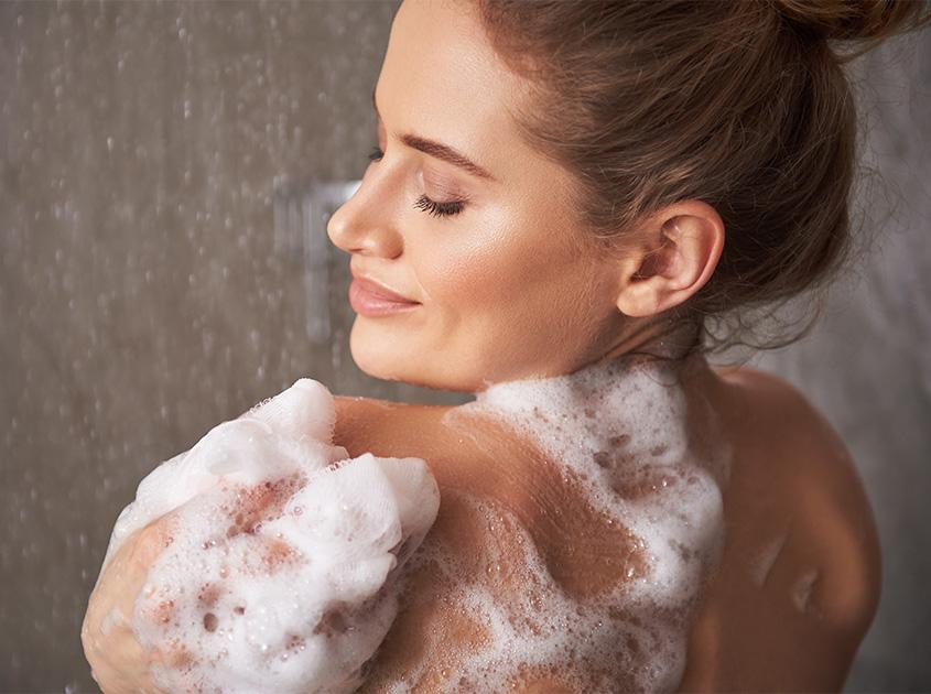 Frau beim Duschen mit weichem Schaum