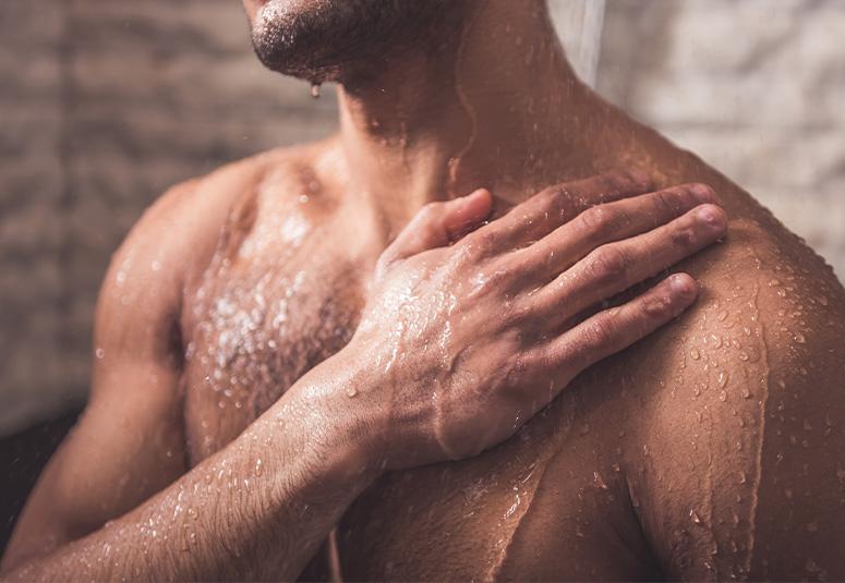 Brust bis Kinn eines Mannes von vorne unter der Dusche. Rechter Hand auf Schulter.