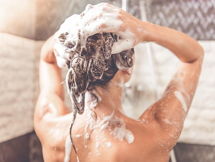 Frau von Hinten unter der Dusche am Haare einseifen.