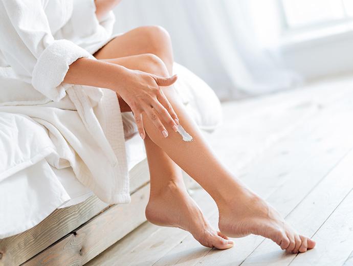 Eine Frau im weissen Bademantel sitzend auf einem Bett mit weissen Lacken. Helle Stimmung. Bett und Fussboden aus Holz. Von der Frau sind nur die Beine und Arme zu sehen. Sie trägt sich Bodylotion auf die Beine.
