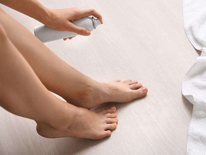 Frau sprayt Ihre Füsse ein.